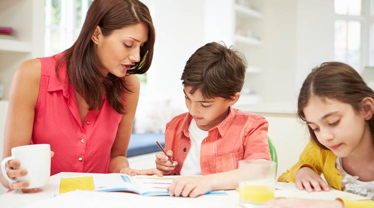 Hispanic Mother Helping Young Children With Homework