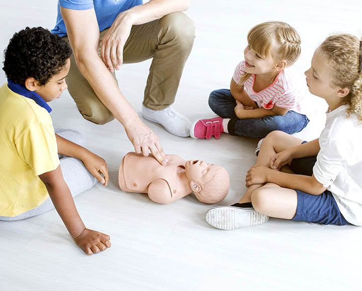 Multicultural group of children learning first aid on baby's manikin with paramedic