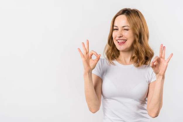 young-woman-biting-her-tongue-showing-ok-gesture-with-two-hands-winking_23-2148055915